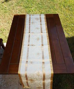 Stoni raner bež organdin sa zlatnim detaljima na stolu